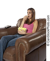 Movie night watching TV eating popcorn - Young woman sits in...