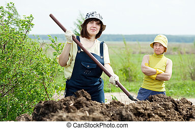 farmers works with manure at field - Female farmers works...