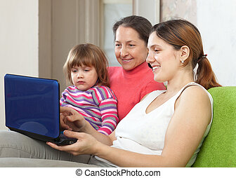 Family of three generations with laptop