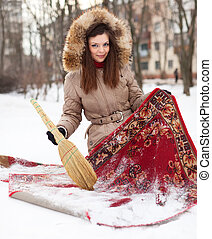 woman cleans red carpet with snow in winter outdoor