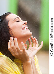 woman having fun in the rain - happy young woman having fun...