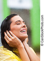 woman enjoying rain outdoors - attractive young woman...