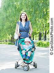 mother with stroller in summer park