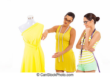 two dressmakers working together on white