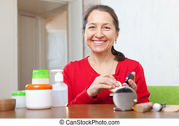 mature woman puts facepowder - Smiling mature woman in red...
