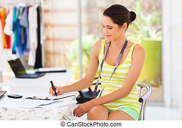 pretty young fashion designer sketching in her studio