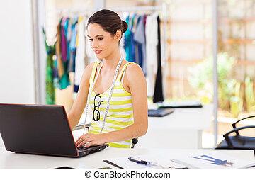 fashion designer sketching using laptop