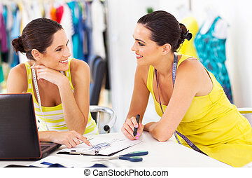 two happy fashion designers discussing new design in studio