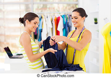 two young female fashion designers choosing fabric