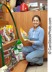 woman chooses fertilizers at garden shop - Smiling mature...