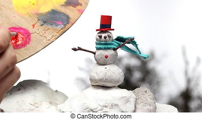painting a snowman puppet - man painting buttons on a...
