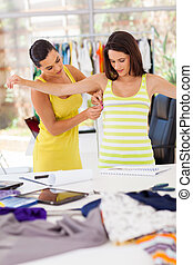 dressmaker measuring clients bust size - female dressmaker...