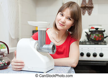 Woman with electric mincer in kitchen