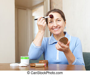 mature woman puts facepowder on face - Happy mature woman...