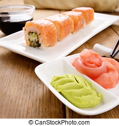 Philadelphia roll sushi on a white plate with soy sauce...