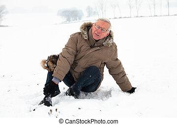Senior man with injured leg on snow - Unhappy senior man...