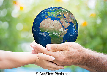 Earth day - Child and senior man holding planet Earth in...