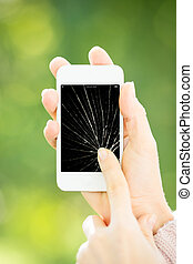 Woman holding smartphone with broken touchscreen
