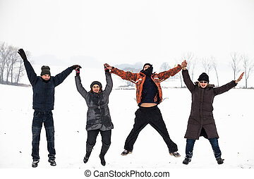 Happy people jumping in snow winter