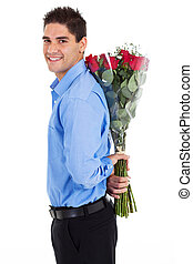 young man hiding roses - young man hiding bunch of red roses...