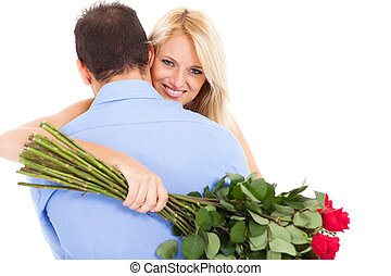 young woman hugging boyfriend with bunch of roses