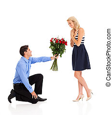 young man down on his knee to give bunch of roses to a woman