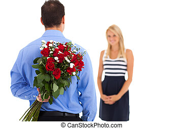 young man hiding bunch of roses behind his back to surprise...