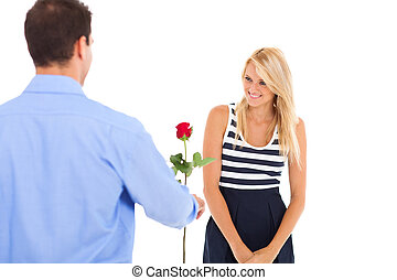 young man giving rose to a beautiful young woman