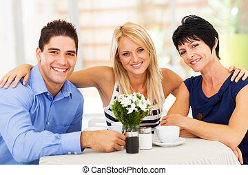 man with wife and mother-in-law in cafe - happy young man...
