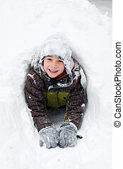 young boy playing outdoors on a snowy winter day