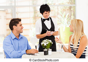 friendly middle aged waitress taking order from customer in...