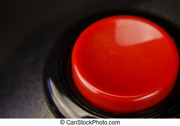 Red firing button (on a black joystick) on black surface.