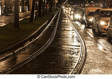 wet trolley rails in the light and streets are reflecting...