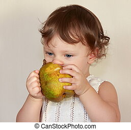 Baby eating fruit pear isolated on white background. Healthy food