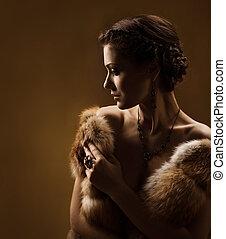 Woman in luxury fur coat. Vintage style. Brown background.
