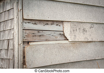Peeling wood siding - Wooden boards falling off an old home