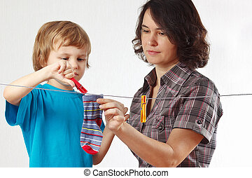 Mother with her son hanging clothes on a white background