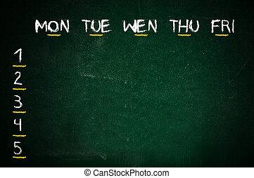 School timetable handwritten on a green classroom chalkboard