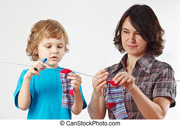 A little boy helps her mother to hang up your socks
