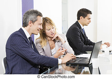 Bureau - Businesspeople looking at laptop in meeting room.