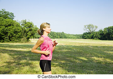 jogging - Young blond woman jogging on pathway in park,...