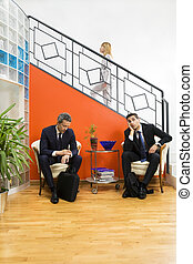 Bureau - Businessmen waiting in office. Woman stepping up...