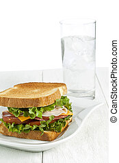 a plate with ham sandwich and a glass of water