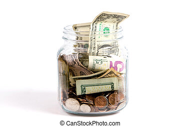 Tip Jar - US dollars and coins fill a glass tip jar with...