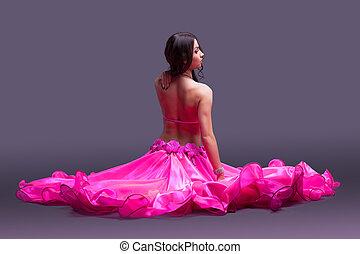Dancer in pink costume sitting on floor