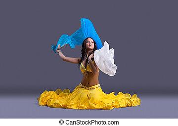 Beautiful dancer in yellow costume sit on floor