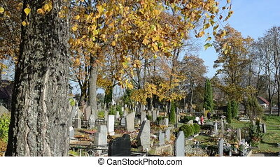 people care family graves in beautiful autumn cemetery...