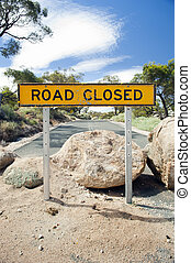 Road Closed Sign - Road closed sign with large boulders on...