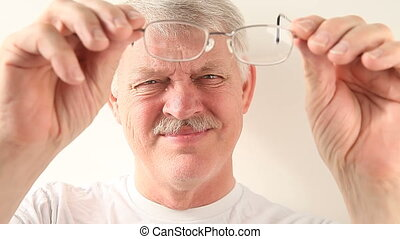 man cleans his glasses