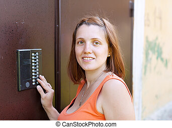 woman using house intercom outdoor - Young woman pushing...